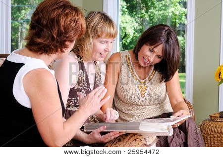 Middle Age Woman Showing Her Family Photo Album To Her Friends