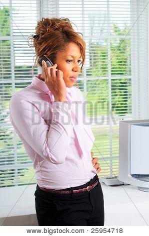 Mulher bonita fazendo uma chamada de telefone celular em seu escritório