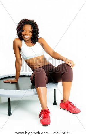 Bela mulher afro-americana feliz vestida de Fitness no ginásio Sat sobre um trampolim