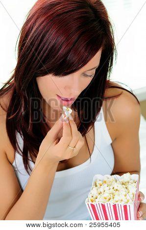 Beautiful Young Woman Eating Popcorn Wearing Pajamas