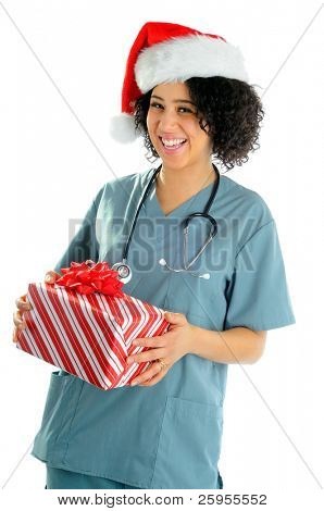 African American Hospital Nurse Holding A Christmas Gift Wearing Scrubs And a Santa Hat For The Holidays