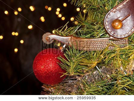Cowboy Christmas - spur with a red ball ornament, decorating the tree