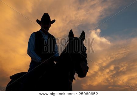 Silhouette of a horse and a rider against dramatic evening storm clouds