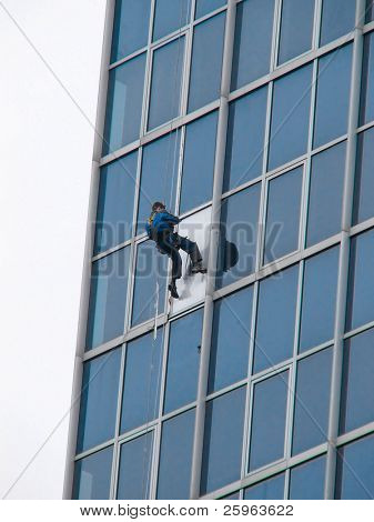 Window washer or  man fixing windows on tall building