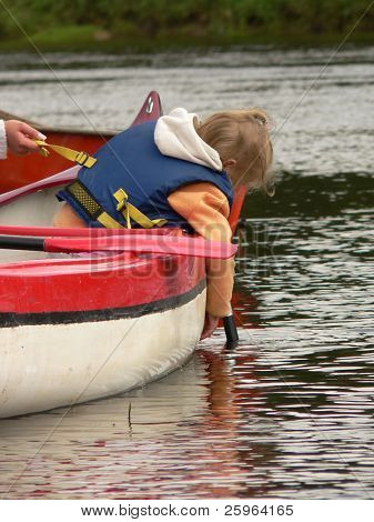 Kid danger play with water in canoe, but mummy hold/protect her child