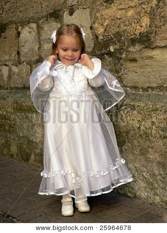 Jumping girl in Christening Gown. Soft focused face
