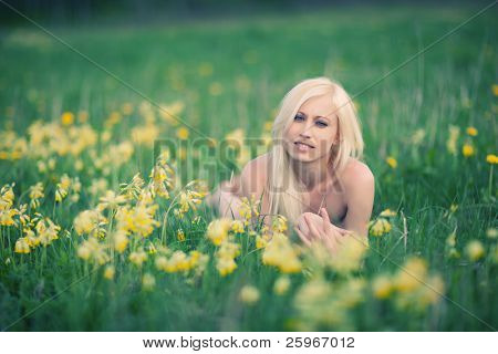 Girl lays in larkspur field, very happy and cute portrait
