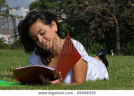 Pregnant young mum on a grass in park writes in a writing-book