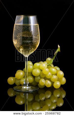 wineglass with white wine and grapes on a black background