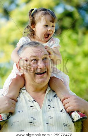 The grandfather with grand daughter in park