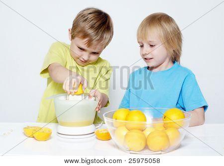 Children squeeze out orange juice
