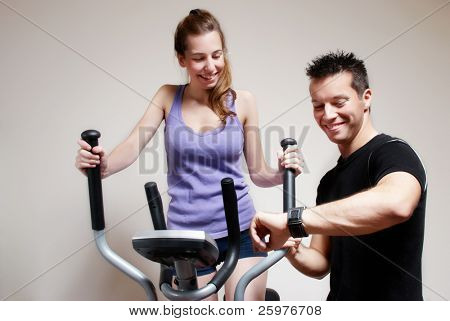 Girl on training apparatus and instructor in sportclub