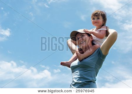 The mother with small daughter against sky