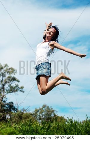 Happy young girl jumping in nature