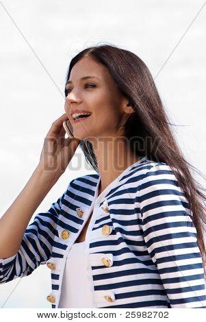 Closeup Retrato de una bella mujer joven sonriente hablando por teléfono móvil