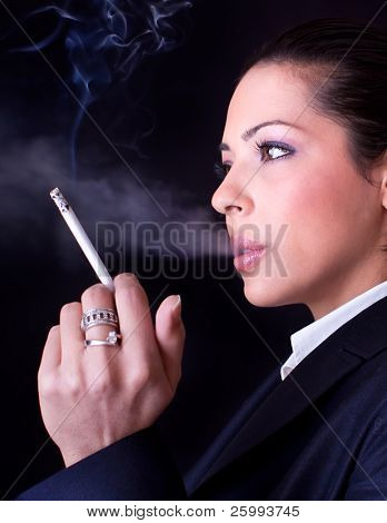 Close up business woman with cigarette .Photo-session in studio isolated on black background