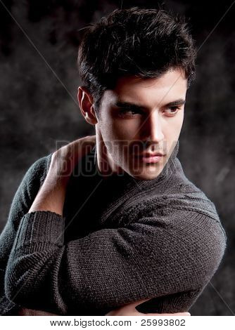 Pretty young man posing on dark background
