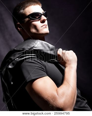 fashion male whit sunglasses hold black jacket ,   dark background