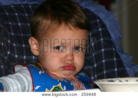 Toddler In High Chair Making A Pouting Face