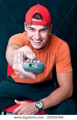 Hombre joven con un mando cambio de televisora