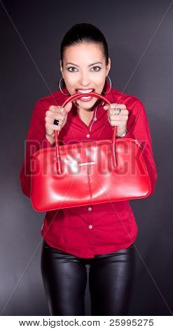 Beautiful young woman with red bag in teeth, studio shot