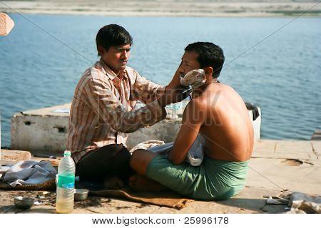 VARANASI, INDIA -FEBRUARY 10: Street barber shaving a man using an open razor blade on a bank of sacred river Ganges in Varanasi . February 10, 2008, Varanasi, India.