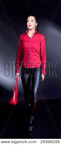 Beautiful brunette with red shirt and red bag  walking , studio shot