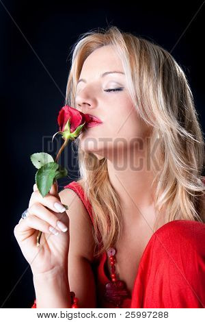 Beautiful woman smelling red blossom of roses