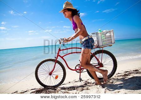 Beautiful caribbean woman with bicycle waking on a topical beach