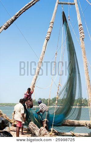 COCHIN, Indien - Februar 02: Sammeln Fischer ihren Fang aus der traditionellen chinesischen Fischerei net auf