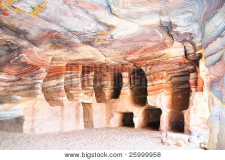 One of many amazing rainbow-coloured hollows of tombs and caves in ancient city of Petra, Jordan