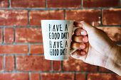 Close Up Of Male Hand Holding White Coffee Or Tea Cup With Text have A Good Day! On Old Red Brick  poster