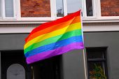 Rainbow Flag Waving In City At Pride Parade - Lgbt Symbol - For Gay, Lesbian, Bisexual Or Transgende poster