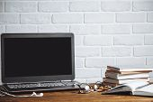 Workspace Of Business Man Or Student - Laptop, Notebooks, Pen, Books, Earphones On Wooden Desk poster