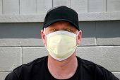 stock photo of the mexican swine flu  - a man wears a yellow medical paper mask as he looks around to stay safe from any air born illness - JPG