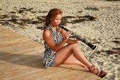 Постер, плакат: привлекательный Афроамериканец женщина играет ее Кларнет вне на пляже для всех чтобы слышать и Панси