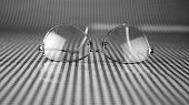 old gold framed prescription reading glasses lay upon a black and white background waiting for the o