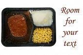 a classic salisbury steak tv dinner with mashed potatoes and corn in its black plastic tray, isolate