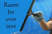 stock photo of window washing  - a window washer soaps and cleans a window with a squeegee with room for your text - JPG