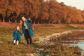 Mother And Daughter Walking Near River In Autumn Time. Happy Family. Fall Weekend In The Open Air. F poster