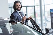 Portrait Of Smiling Businessman With Car Key Standing At New Car At Dealership Salon poster