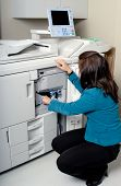 Young Woman Doing Routine Maintenance On An Office Photocopier