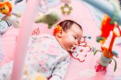 Cute Baby Girl On Colorful Gym, Playing With Hanging Toys At Home, Baby Activity And Play Center For poster