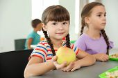 Children Sitting At Table And Eating Healthy Food During Break At School poster