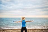 Young Sporty Woman Runner With Elastic Bands Outside On A Beach, Exercising. poster