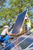 Two Technicians Standing On Metal Platform Adjusting Heavy Solar Photo Voltaic Panel On Bright Sunny poster