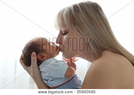 Mother kissing newborn