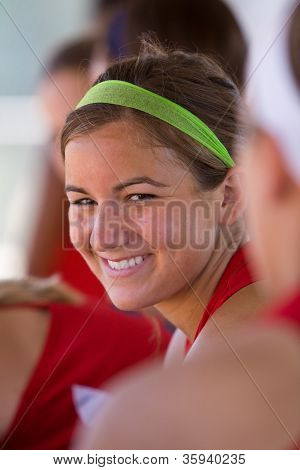 Female Softball Player Smiles From Inside Dugout