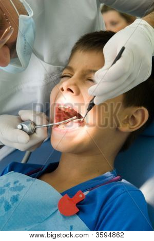 Dentist Fixing The Cavities Of A Young Boy