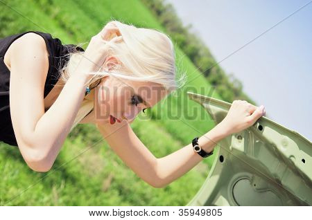 Blonde Girl Stands By The Broken Car
